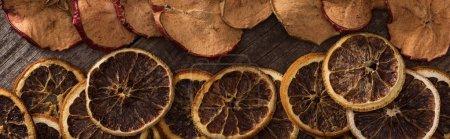 plan panoramique de tranches d'orange et de pomme séchées sur fond de bois