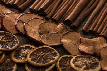 dried orange and apple slices with cinnamon on wooden background