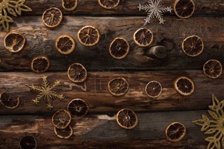 top view of dried citrus slices and decorative snowflakes on wooden background