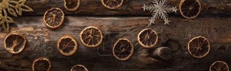 Foto de Vista superior de las lonchas secas de cítricos y de los copos decorativos de nieve sobre fondo de madera, tiro panorámico. - Imagen libre de derechos