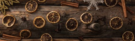 top view of dried citrus slices with anise, cinnamon sticks and decorative snowflakes on wooden background, panoramic shot