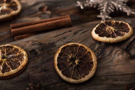 Foto de Rodajas de cítricos secos, varillas de canela y copo de nieve decorativo sobre fondo de madera - Imagen libre de derechos