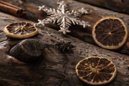 Photo for Dried citrus slices with decorative snowflake on wooden background - Royalty Free Image