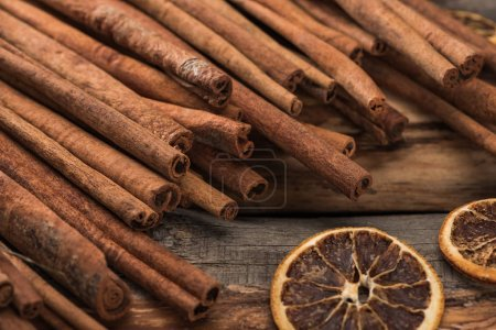 Photo for Cinnamon sticks near dried citrus slices on wooden background - Royalty Free Image