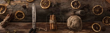 flat lay with cinnamon sticks, scissors, ball of thread on wooden background with winter decor, panoramic shot