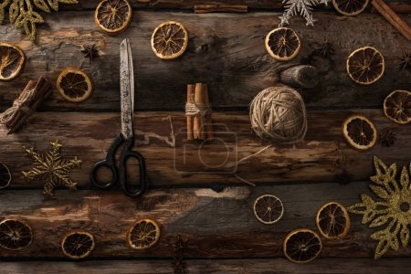 Photo for Flat lay with cinnamon sticks, scissors, ball of thread on wooden background with winter decor - Royalty Free Image