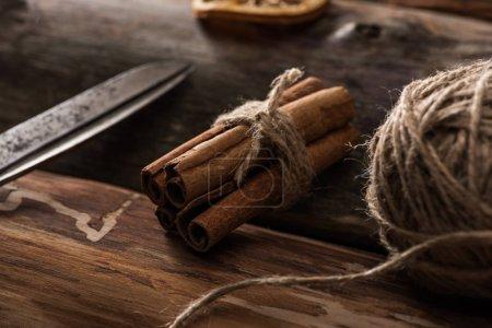 vue rapprochée des bâtons de cannelle, ciseaux, boule de fil sur fond en bois