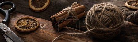 vue rapprochée des bâtons de cannelle, ciseaux, boule de fil sur fond bois avec tranches d'agrumes séchées, vue panoramique