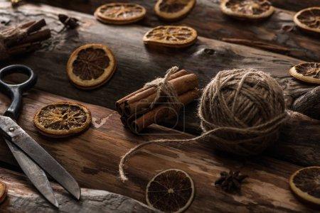 anis, bâtonnets de cannelle, ciseaux, boule de fil sur fond bois
