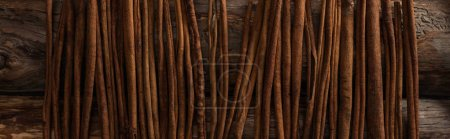 Photo for Top view of cinnamon sticks on wooden background, panoramic shot - Royalty Free Image