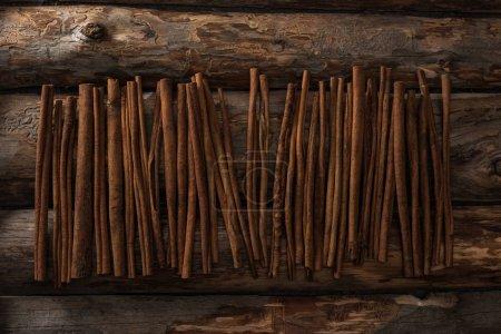 Photo pour Vue de dessus des bâtons de cannelle sur fond en bois - image libre de droit