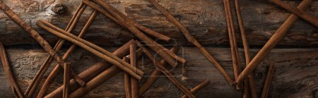top view of cinnamon sticks scattered on wooden background, panoramic shot