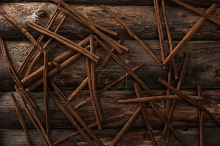 top view of cinnamon sticks scattered on wooden background