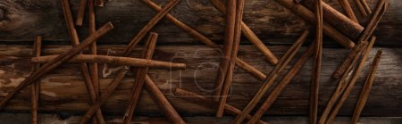 Photo for Top view of cinnamon sticks scattered on wooden background, panoramic shot - Royalty Free Image