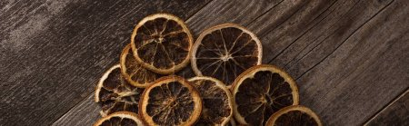 top view of dried citrus slices on wooden brown surface