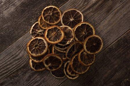 Photo pour Vue de dessus des tranches d'agrumes séchées sur la surface brun bois - image libre de droit