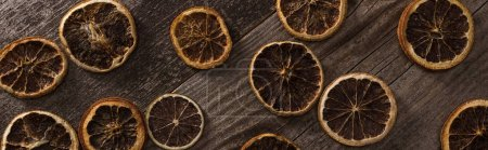 Photo for Top view of dried citrus slices on wooden brown surface, panoramic shot - Royalty Free Image