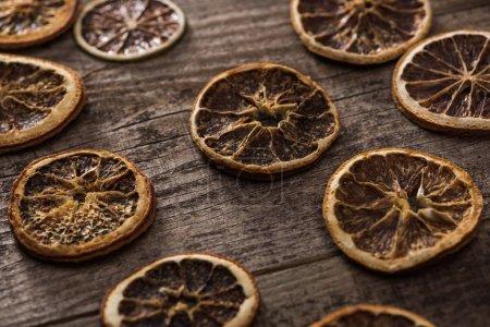 Photo pour Tranches d'agrumes séchées sur une surface brune en bois - image libre de droit