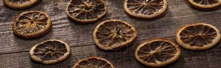 dried citrus slices on wooden brown surface, panoramic shot