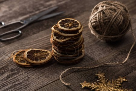 selective focus of thread, scissors and dried citrus slices, snowflake on wooden background