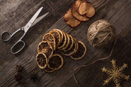 Photo pour Vue de dessus du fil, des ciseaux et des tranches d'agrumes et de pommes séchées sur fond en bois avec flocon de neige - image libre de droit