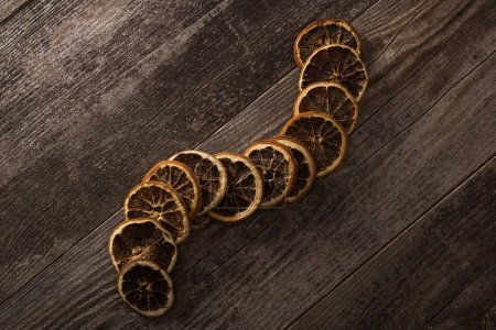 vista superior de rebanadas de naranja secas sobre fondo de madera