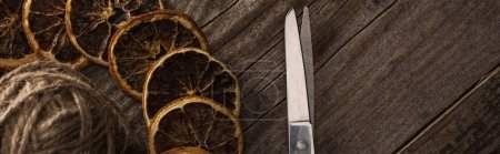 Photo for Top view of thread, scissors and dried citrus slices on wooden background, panoramic shot - Royalty Free Image