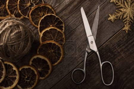 top view of thread, scissors, snowflake and dried citrus slices on wooden background