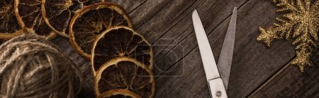 Photo for Top view of thread, scissors, snowflake and dried citrus slices on wooden background, panoramic shot - Royalty Free Image