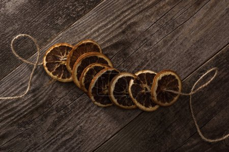 vista superior de rebanadas de naranja secas en la cuerda en la superficie de madera