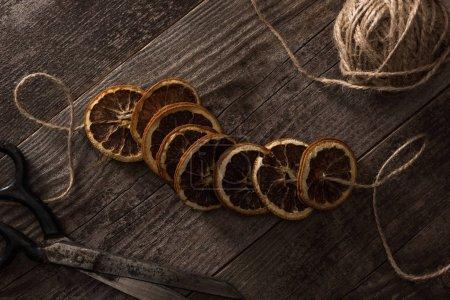 Photo pour Vue du dessus du fil, des ciseaux et des tranches d'agrumes séchées sur fond en bois - image libre de droit