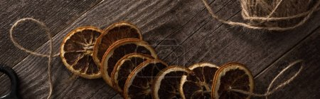 Photo for Top view of thread with dried citrus slices on wooden background, panoramic shot - Royalty Free Image