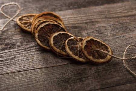 Photo for Dried orange slices on rope on wooden surface - Royalty Free Image