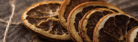 close up view of dried orange slices on rope on wooden surface, panoramic shot
