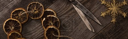 top view of dried citrus slices on rope near snowflake and scissors on wooden surface, panoramic shot