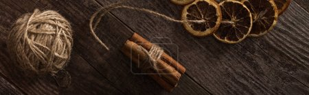 Photo for Top view of dried citrus slices on rope near cinnamon on wooden surface, panoramic shot - Royalty Free Image