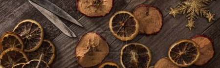 Photo for Top view of dried citrus and apple slices near snowflake, rope and scissors on wooden surface, panoramic shot - Royalty Free Image