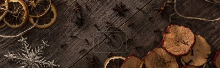 Photo for Top view of dried citrus and apple slices near snowflake and anise on wooden surface, panoramic shot - Royalty Free Image