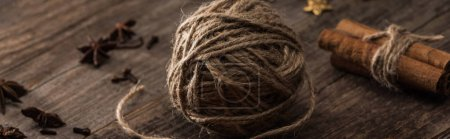 panoramic shot of ball of thread and cinnamon on wooden surface