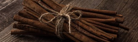 Photo for Cinnamon sticks in bunch on wooden rustic table, panoramic shot - Royalty Free Image