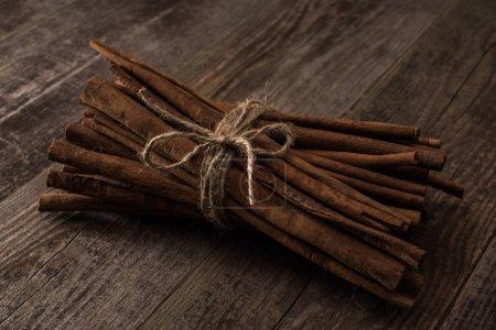 Photo pour Bâtons de cannelle en bouquet sur table rustique en bois - image libre de droit
