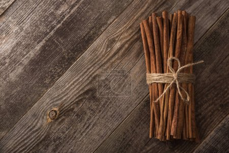 Photo for Top view of cinnamon sticks in bunch on wooden rustic table with copy space - Royalty Free Image