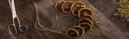 Photo for Top view of dried citrus slices on rope near snowflake, scissors on wooden surface, panoramic shot - Royalty Free Image