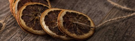 Photo for Dried orange slices on thread on wooden table, panoramic shot - Royalty Free Image