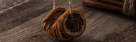 Photo for Dried orange slices on thread and cinnamon on wooden background, panoramic shot - Royalty Free Image