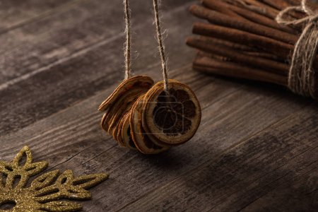 Photo for Dried citrus slices on thread near cinnamon and snowflake on wooden background - Royalty Free Image
