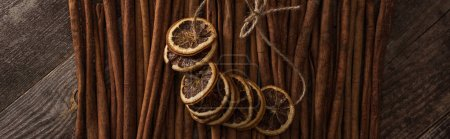 Photo for Top view of dried orange slices on thread and cinnamon on wooden background, panoramic shot - Royalty Free Image