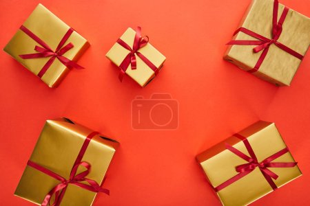Photo pour En haut des boîtes-cadeaux dorées sur fond rouge - image libre de droit
