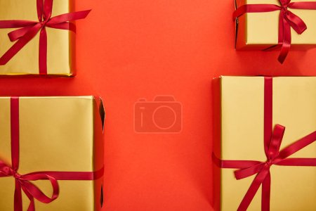 Photo for Flat lay with golden gift boxes on red background with copy space - Royalty Free Image