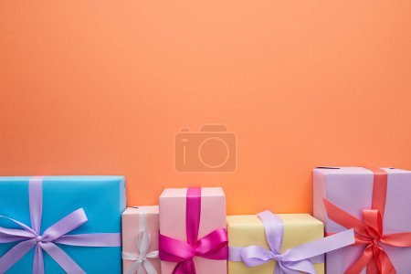 Photo for Flat lay with multicolored gift boxes with ribbons and bows on orange background with copy space - Royalty Free Image